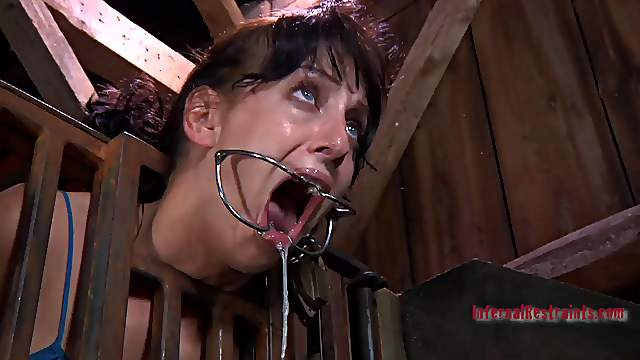 Caged slave having her mouth widened in BDSM torture