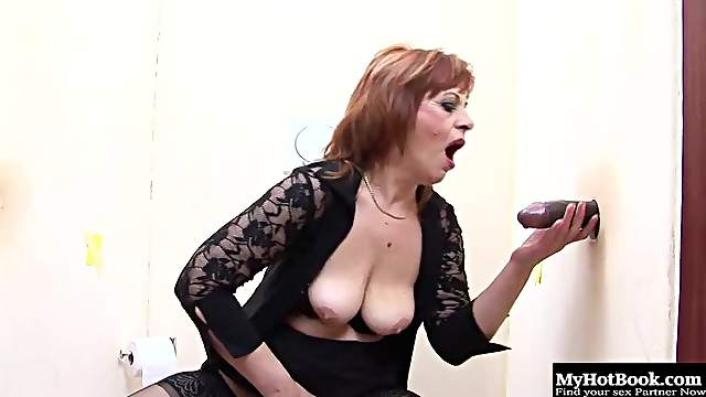 Redhead mature slag fingers her twat and sucks on a gloryhole cock