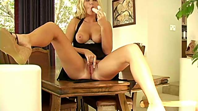 Fair haired babe sits on a table while she toy fucks her juicy snatch